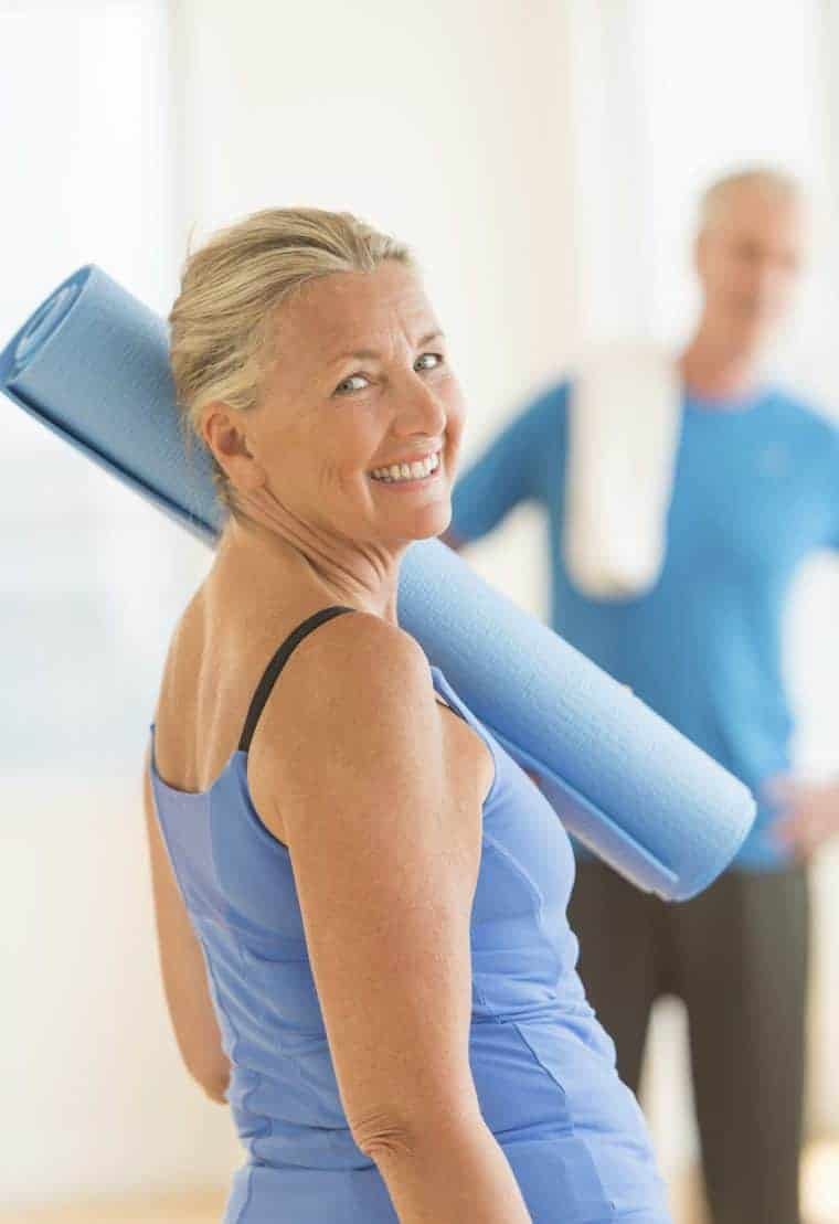 Senior Woman With Exercise Mat At Home